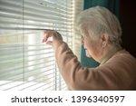 Senior Woman Spying Through...