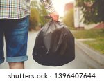 Young man taking out garbage in ...