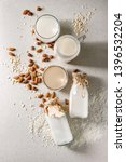 Small photo of Variety of non-dairy vegan lactose free nuts and grain milk almond, hazelnut, coconut, rice, oat in glass bottles with ingredients above over white spotted background. Flat lay, space