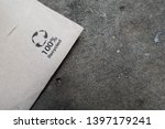 Small photo of Barcelona,Catalonia / Spain - May 10, 2019: Unused napkin, serviette lies on a stone table with a one hundred per cent recyclable logo emphasising the need for recycling. Graphic image and copy space