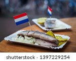 Stock photo traditional dutch street food saline herring with pickles onions and dutch flags in a fish 1397229254