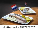 Stock photo traditional dutch street food saline herring with pickles onions and dutch flags in a fish 1397229257