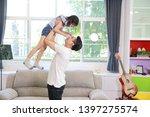 happy asian dad throws his... | Shutterstock . vector #1397275574