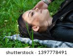 a girl lying down on a blanket... | Shutterstock . vector #1397778491