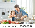 Small photo of Healthy food at home. Happy family in the kitchen. Mother and child daughter are preparing proper meal.
