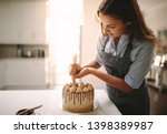 Woman Decorating Chocolate Cak...