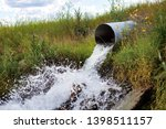 Culvert Spilling Water Splashing out in Grass