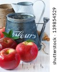 Red ripe apples and watering can in a garden. - stock photo