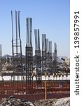 Rebar frames on a building construction site on concrete foundation with orange construction fencing - stock photo