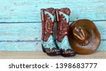 pair of colorful blue and red cowboy boots and hat standing on natural wood with a blue wooden background - stock photo