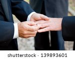 Gay Couple Exchanging Rings At...