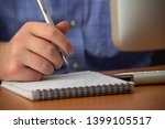 hands of a young man with a pen ... | Shutterstock . vector #1399105517