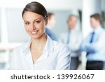 Stock photo happy businesswoman with colleagues in the background 139926067