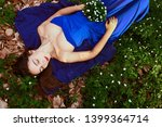 a calm girl lies on the grass... | Shutterstock . vector #1399364714