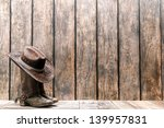 American West rodeo brown felt cowboy hat atop worn and dirty traditional leather boots on a wood deck in front of a vintage ranch barn weathered plank wall - stock photo