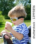 Boy in Swimming Goggles drinking soda from a mug - stock photo