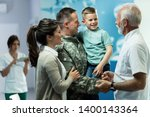 Happy senior doctor talking to little boy who came with mother and military father at clinic. Focus is on military man.