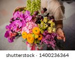 Small photo of Girl sitting near a spring box of tender yellow, green and violet flowers decorated with pink bow