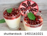 Pomegranate fruit and a creamy dessert with pomegranate seeds - stock photo