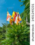 Three Colorful Flags Over Gree...