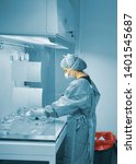 Small photo of Scientific woman working on extraction hood with face mask, hat, gloves and plastic pretreatment dress