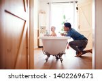 father washing small toddler... | Shutterstock . vector #1402269671