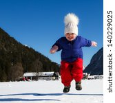 Toddler Girl Jumping In Snow.
