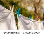 Stock photo white clothes hung out to dry on a washing line and fastened by the clothes pegs in the bright warm 1402492934