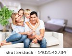 young  family at home smiling... | Shutterstock . vector #1402542734