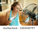 Small photo of unhappy housewife in the modern house in sunny hot summer day in the front of working fan suffering from summer heat
