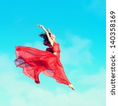 Woman in airy red dress jumping in the air, blue sky background - stock photo