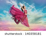 Woman in airy crimson dress jumping in the air at sunset - stock photo