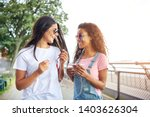 two smiling young girlfriends... | Shutterstock . vector #1403626304