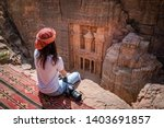 Small photo of Asian woman traveler sitting on carpet viewpoint in Petra ancient city looking at the Treasury or Al-khazneh, famous travel destination of Jordan and one of seven wonders. UNESCO World Heritage site.