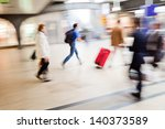 walking people in motion blur in the shopping area of a railway station - stock photo