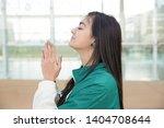 focused positive girl praying... | Shutterstock . vector #1404708644