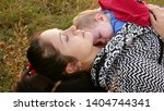 young mother lies in the grass... | Shutterstock . vector #1404744341
