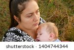 young mother lies in the grass... | Shutterstock . vector #1404744344