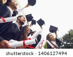 Small photo of Happy graduates raised their hands with scrolls of diplomas