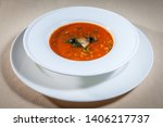 Stock photo upper view on white bowl on big saucer with solaynka decorated with piece of salted herring and few 1406217737