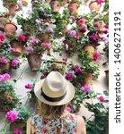 woman admiring flowers in... | Shutterstock . vector #1406271191