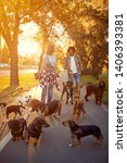 Stock photo girl and man dog walker walking with a group dogs in the park 1406393381
