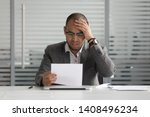 Small photo of Frustrated upset african businessman reading bad news in paper mail letter got fired feel stressed sad desperate about problem bank debt dismissal notification rejection denial sitting at office desk
