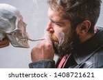 Small photo of Harmful habits. Smoking is harmful. Habit to smoke tobacco bring harm to your body. Smoking cause health damage and death. Man smoking cigarette near human skull symbol death. Nicotine destroy health.