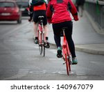Persons on bikes seen from behind, in rain - stock photo