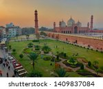 Badshahi masjid known as kings mosque in lahore at evening with kids playing in mosque's garden and with the lahore city in background