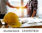 Small photo of yellow safety helmet on workplace desk with construction worker team hands shaking greeting start up plan new project contract in office center at construction site, partnership and contractor concept