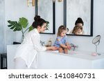 a young woman and a baby wash... | Shutterstock . vector #1410840731