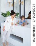 a young woman and a baby wash... | Shutterstock . vector #1410840734