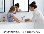 a young woman and a baby wash... | Shutterstock . vector #1410840737